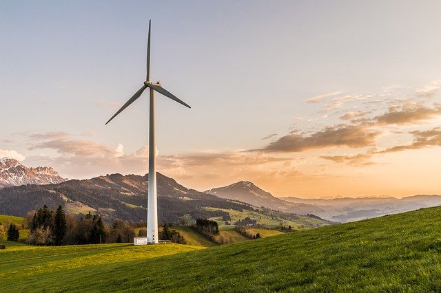 A windmill in a field with a mountain in the background
